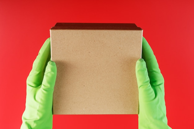 The parcel from the delivery service in the hands with green rubber gloves on a red background. Premium Photo