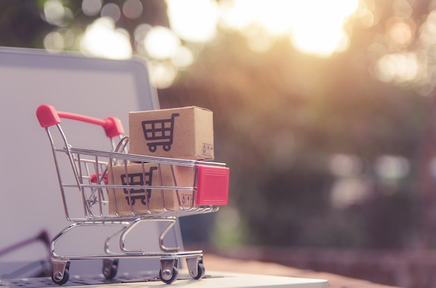 Parcel or paper cartons with a shopping cart logo in a trolley on a laptop keyboard. Premium Photo