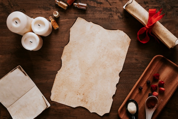 Parchment near candles and ingredients Free Photo