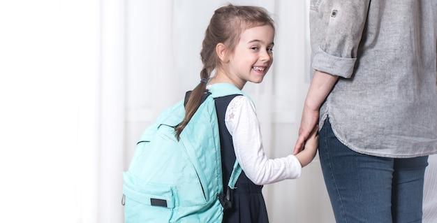 Родитель и ученик начальной школы идут рука об руку на светлом фоне. снова в школу концепции Бесплатные Фотографии