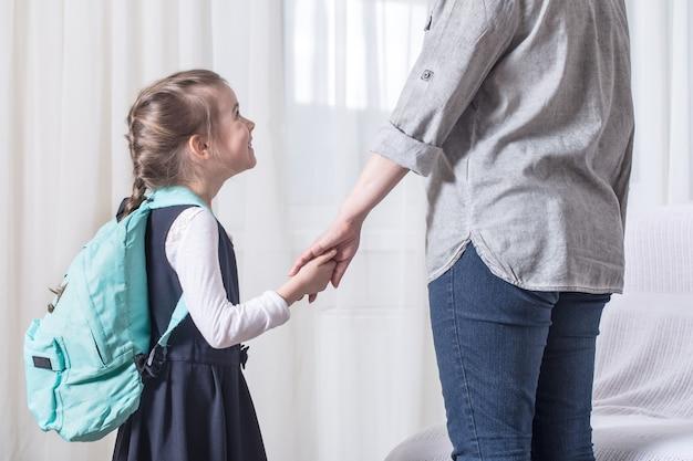 Родитель и ученик начальной школы идут рука об руку Бесплатные Фотографии