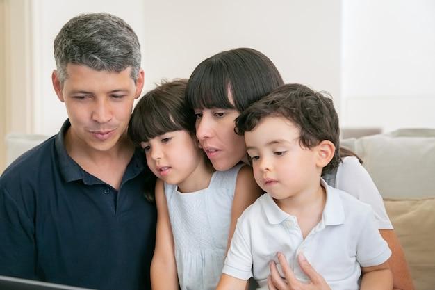 親カップルと2人の子供がコンピューターをビデオ通話に使用し、一緒にソファに座って、ディスプレイを見ている 無料写真
