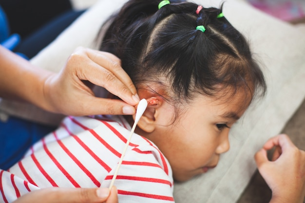 Parent helping her child perform first aid ear injury after she has been an accident Premium Photo