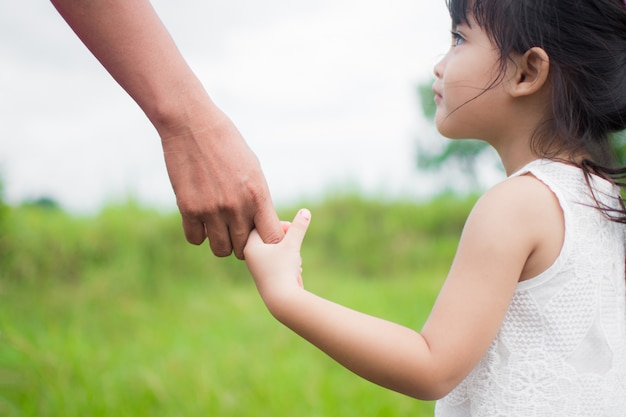 A parent holds the hand of a small child, outdoor nature Premium Photo