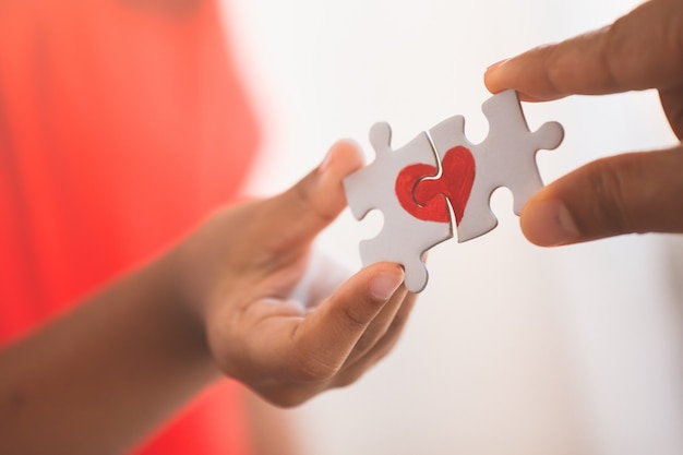 Parent and kid hands connecting couple jigsaw puzzle piece with drawn red heart Premium Photo