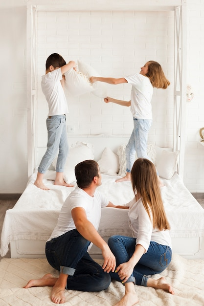 Parent looking at their kids fighting on bed at home Free Photo