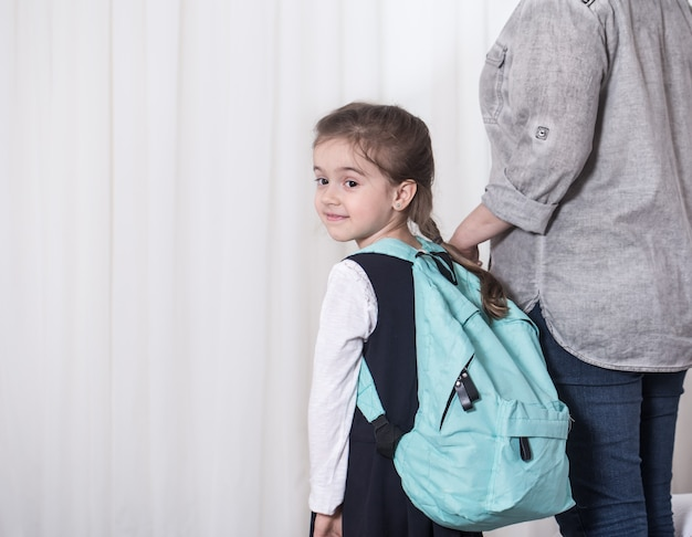 Parent and primary school student go hand in hand Free Photo