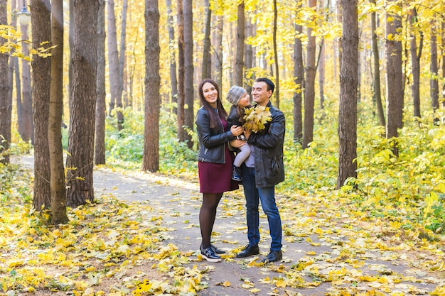 親子関係、秋、人々の概念-秋の公園で幸せな若い家族。 Premium写真