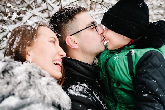 親子関係、ファッション、季節、人々の概念-公園で屋外を歩く冬服を着た子供と幸せな家族。メリークリスマスを祝うというコンセプト。 Premium写真