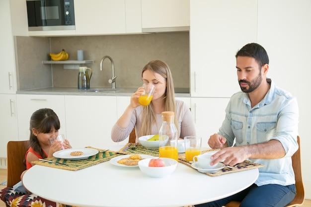 朝食を持っている親子、オレンジジュースを飲む、フルーツとビスケットのダイニングテーブルに座っています。 無料写真
