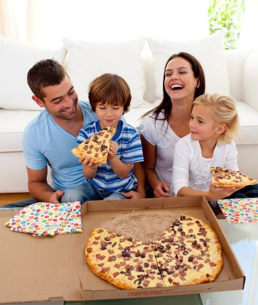 Родители и дети едят пиццу в гостиной Premium Фотографии