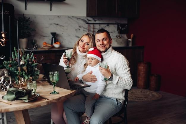 クリスマスディナーを食べながらラップトップを使用しながら眼鏡を保持しているサンタの帽子の両親とかわいい子供 無料写真