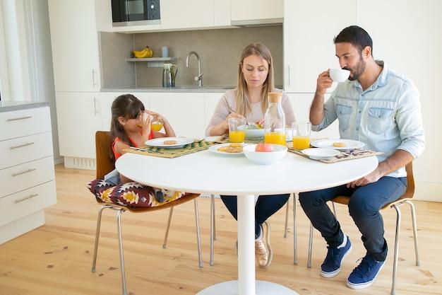 両親と娘が一緒に朝食をとり、コーヒーとオレンジジュースを飲み、フルーツとビスケットのダイニングテーブルに座っています。 無料写真