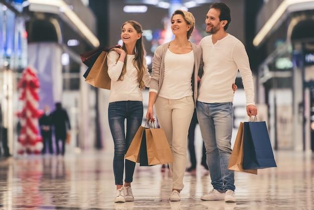両親とその娘は買い物袋を持っています。 Premium写真