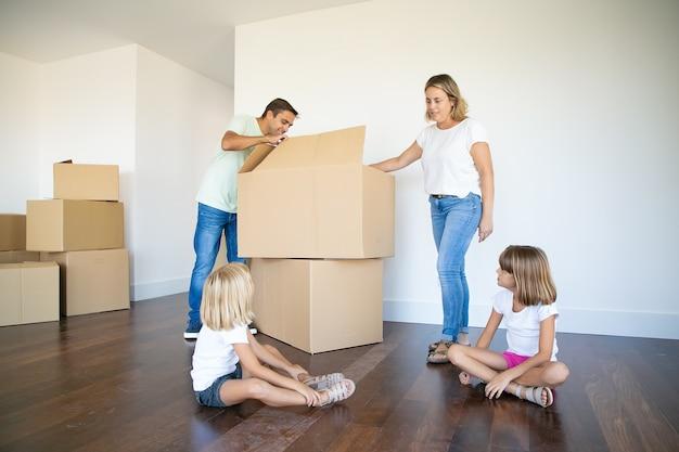 부모와 두 딸이 새 빈 아파트에서 상자를 열고 물건을 풀고 있습니다. 무료 사진