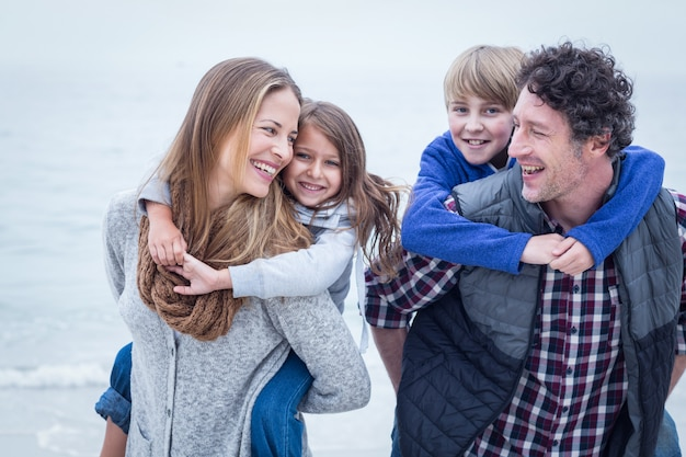 Parents carrying children at beach Premium Photo