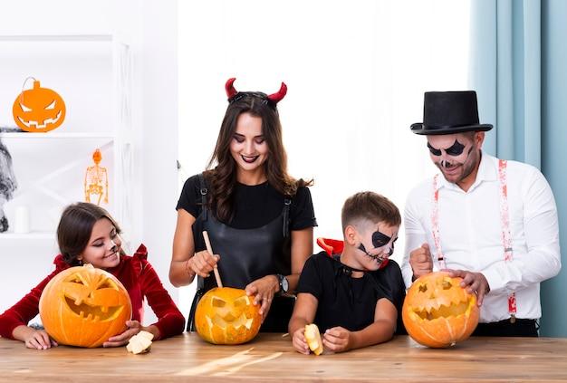 Parents carving pumpkins with children Free Photo