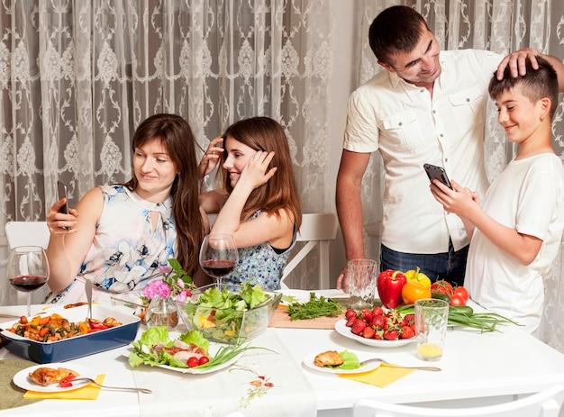 Родители весело проводят время с детьми за обеденным столом Бесплатные Фотографии