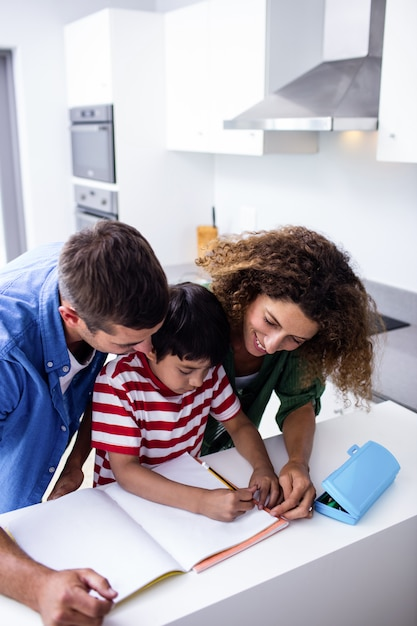 Parents helping son with homework Premium Photo