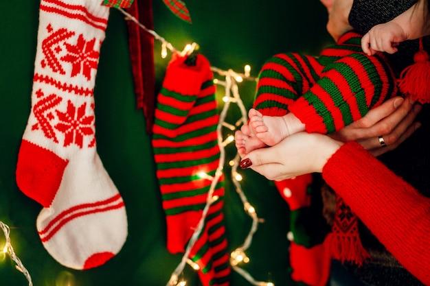 I genitori tengono i piedi dei bambini davanti a una ghirlanda luminosa Foto Gratuite