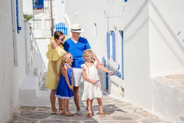 Parents and kids taking selfie photo background mykonos town in greece Premium Photo
