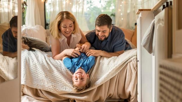 Родители играют с сыном в постели фургона Бесплатные Фотографии