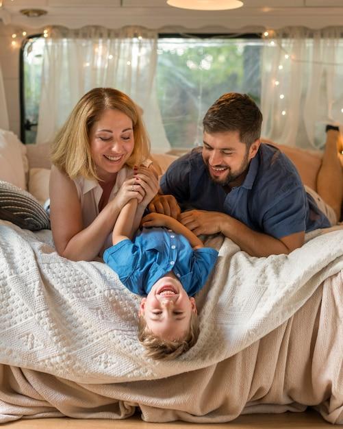 Родители играют с сыном в постели Premium Фотографии