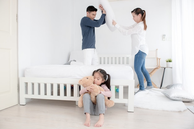 Parents quarrel among themselves. little girl screams and covers his ears with his hands. couple fighting in front of child. Premium Photo