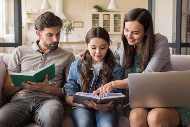 Родители учат девочку читать Бесплатные Фотографии