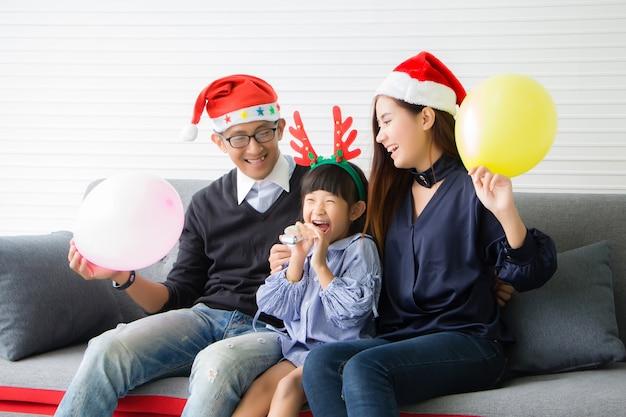 両親は赤いサンタ帽子を、娘は赤い枝角をつけています。彼らはタイ人です。アジアの人々は自宅のリビングルームでクリスマスのお祝いの雰囲気を楽しんでいます。 Premium写真