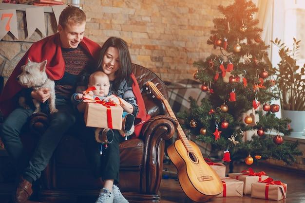 Родители с собакой и ребенком и гитары отдыха на диване Premium Фотографии