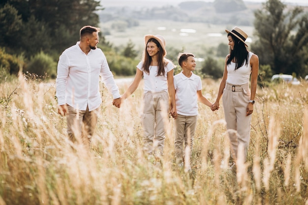 Parents with their children walking in field Free Photo