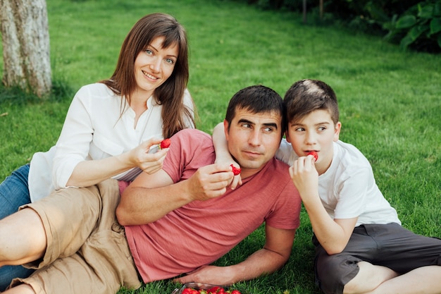 Parents with their son sitting on grass and eating strawberry Free Photo