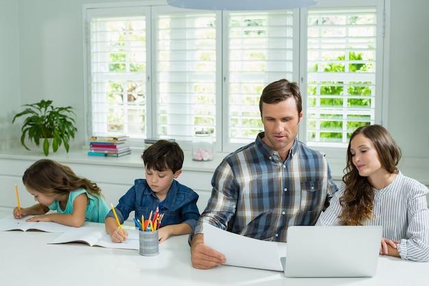 Родители, работающие с ноутбуком, и дети, обучающиеся в гостиной Premium Фотографии