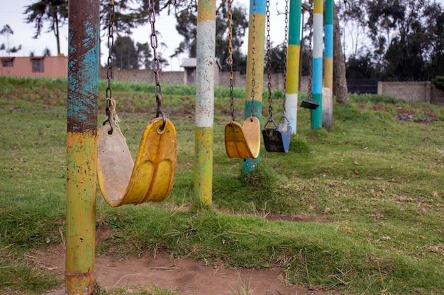 Parco con molte vecchie altalene a catena alterate Foto Gratuite