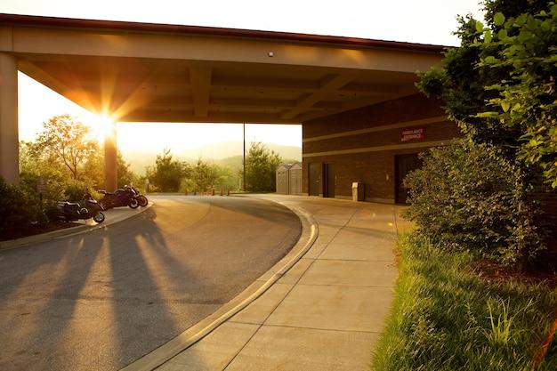 Posto auto immerso nel verde e moto durante il tramonto Foto Gratuite