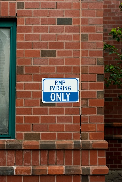 Parking sign on brick wall front view Free Photo
