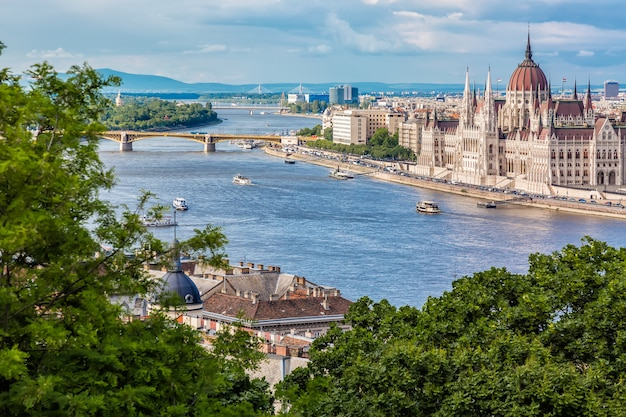 Parliament and riverside in budapest hungary with sightseeing ships during summer sunny day with blue sky and clouds Premium Photo