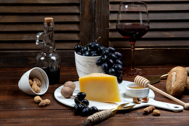 Parmesan slice served with wine and grape Free Photo
