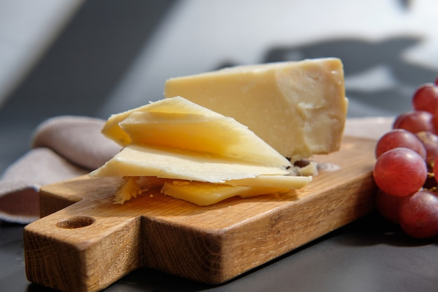 Parmigiano cheese on wooden cut board with grape berries Premium Photo