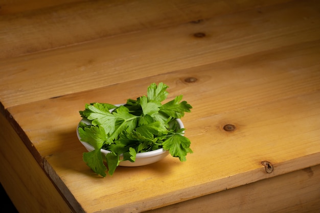 Parsley in a bowl over a wooden table Premium Photo