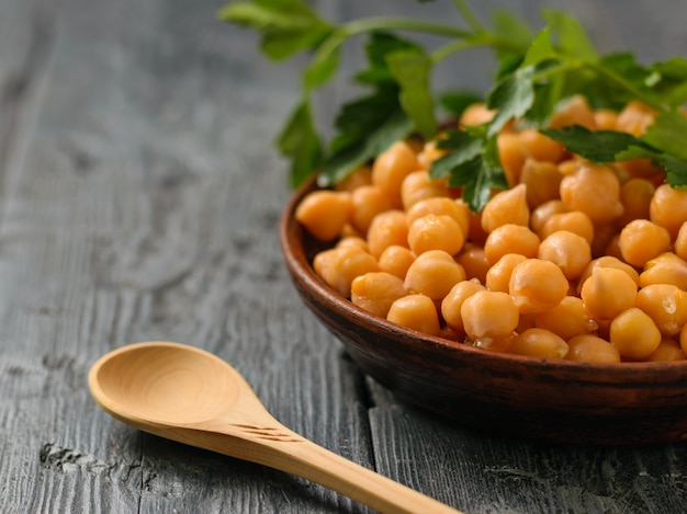 Parsley branch on a bowl with boiled chickpeas on a black table. vegetarian cuisine from legumes. Premium Photo