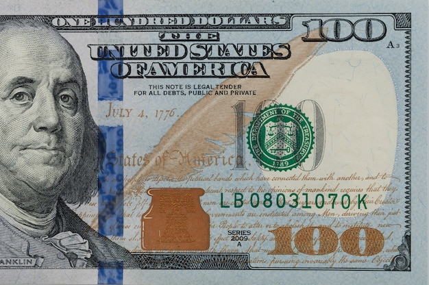 Part of the bill is one hundred us dollars. right part. close-up. Premium Photo