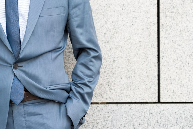 Part of businessman leaning against wall Free Photo