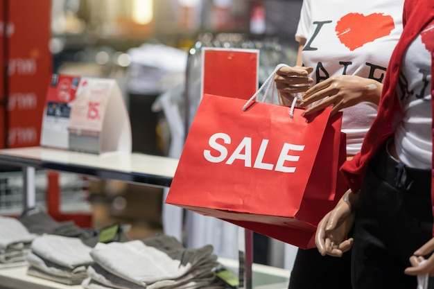 Part of female mannequin dressed in casual clothes holding the sales paper shopping bag Premium Photo