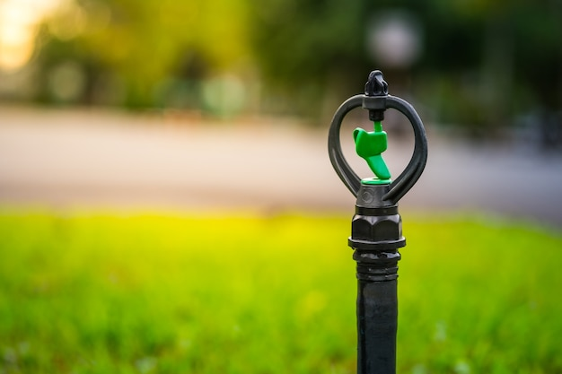 A part of garden sprinkler head located in the public green area background. Premium Photo