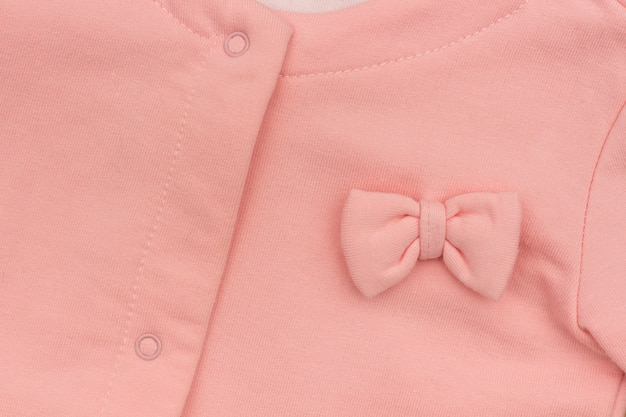 Part girl's pink elegant jacket with bow close-up, background texture Premium Photo