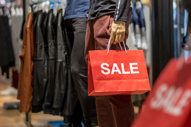 Part of male mannequin dressed in casual clothes holding the sales paper shopping bag Premium Photo