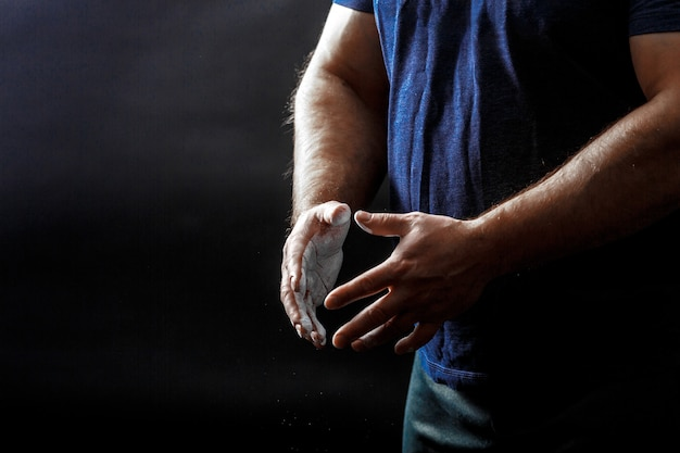 A part of man's torso, wear black t-shirt with hands covered with talcum powder Premium Photo
