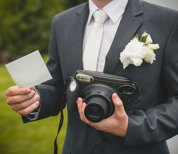 Часть жениха с ретро-камерой и пустой картой Бесплатные Фотографии
